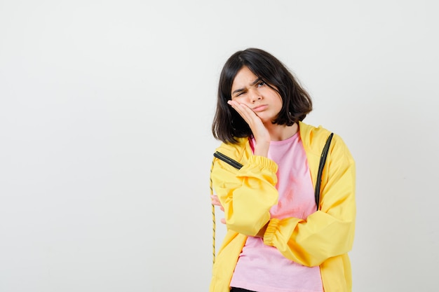 Teen girl hält hand auf wange in t-shirt, jacke und sieht ernst aus, vorderansicht.
