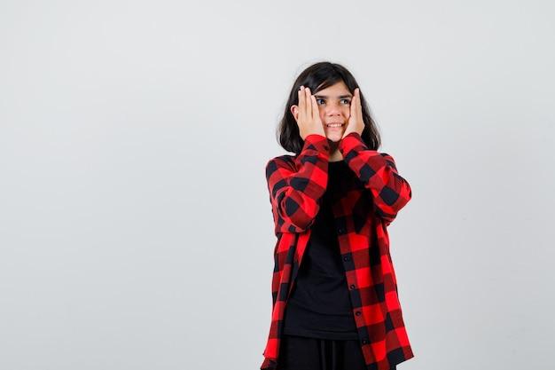 Teen girl hält handflächen auf wangen in freizeithemd und sieht glückselig aus. vorderansicht.