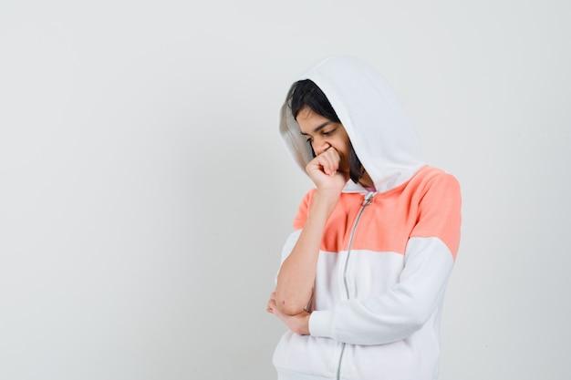 Teen girl im sweatshirt, das nach unten schaut und nachdenklich aussieht.