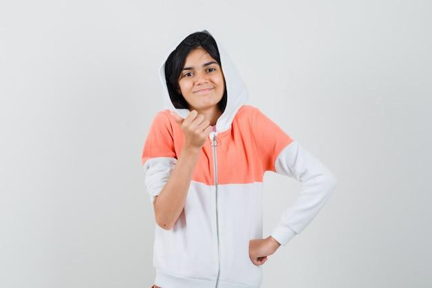 Teen girl in jacke zeigt daumen hoch und sieht positiv aus.