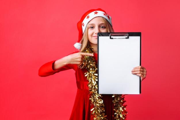 Teen girl in santa hat und lametta am hals zeigt auf die zwischenablage