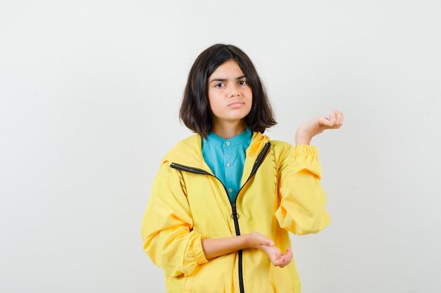 Teen girl macht willkommensgeste in gelber jacke und sieht unentschlossen aus, vorderansicht.