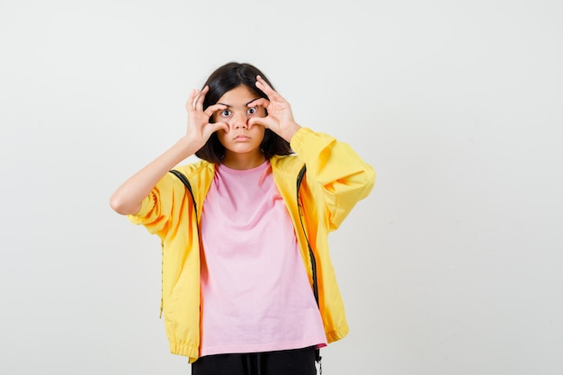 Teen girl öffnet augen mit fingern in gelbem trainingsanzug, t-shirt und sieht überrascht aus, vorderansicht.