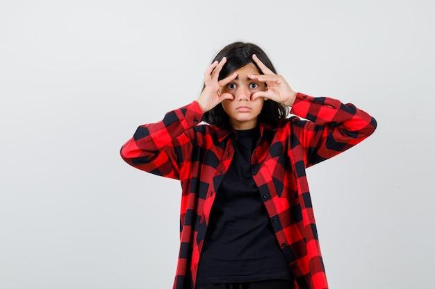 Teen girl öffnet die augen mit den fingern im t-shirt, kariertem hemd und schaut fokussiert, vorderansicht.