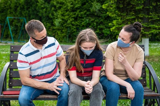 Teen girl und ihre eltern in schützenden gesichtsmasken streiten sich im freien