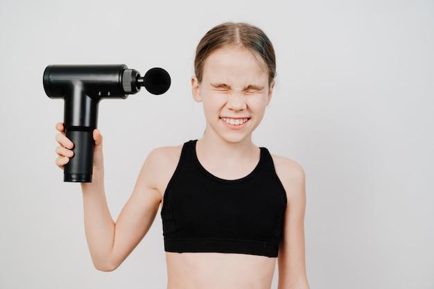 Teen girl verzieht das gesicht und hält massagepistole. medizin-sportgerät hilft muskelschmerzen nach dem training zu reduzieren, hilft müdigkeit zu lindern, wirkt auf problemzonen des körpers, verbessert den hautzustand.
