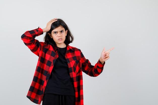 Teen girl zeigt auf die obere rechte ecke, hält die hand auf dem kopf im t-shirt, kariertem hemd und sieht ernst aus. vorderansicht.