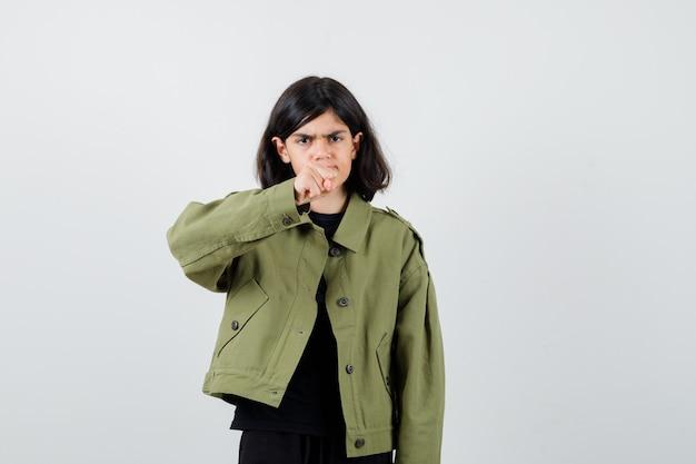Teen girl zeigt geballte faust in t-shirt, jacke und sieht genervt aus, vorderansicht.