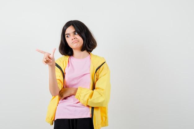 Teen girl zeigt mit dem finger im gelben trainingsanzug, t-shirt und sieht überrascht aus, vorderansicht.