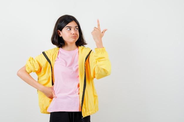 Teen girl zeigt nach oben, hält die hand an der taille im gelben trainingsanzug, t-shirt und sieht unzufrieden aus, vorderansicht.