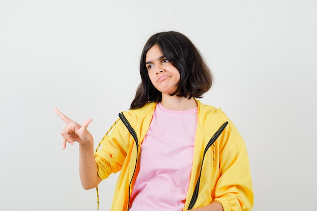 Teen girl zeigt nach oben, schaut zur seite im gelben trainingsanzug, t-shirt und sieht verärgert aus, vorderansicht.