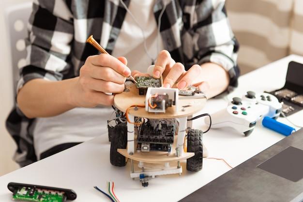 Teen hände programmieren und bauen wissenschaft robotik projekt auf seinem laptop zu hause während covid-19 pandemie lockdown
