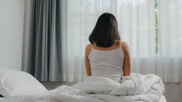 Teen hispanic frau wacht zu hause auf. das junge asiatische mädchen, das nach dem wachen schlaf die ganze nacht beginnt einen neuen tag mit energie und vitalität ausdehnt, fühlte sich auf bett nahe fenster im schlafzimmer am morgen sehr erfrischt.