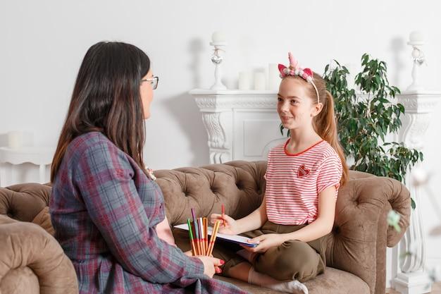 Teen mädchen an der rezeption beim psychotherapeuten. psychotherapie für kinder. der psychologe arbeitet mit dem patienten. das mädchen zeichnet zusammen mit einem arzt bleistift mit bleistift auf papier