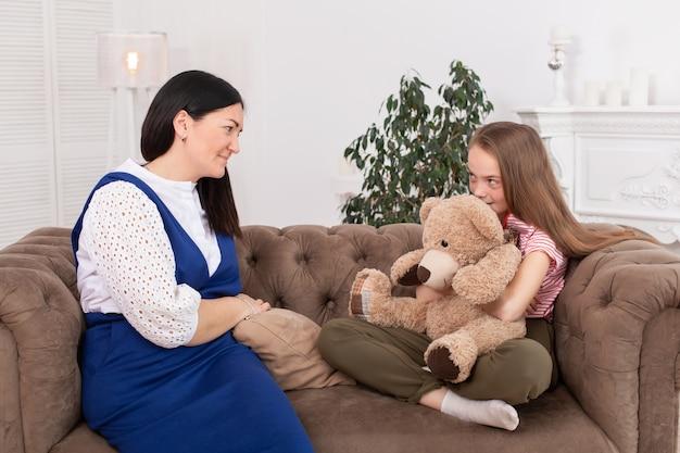 Teen mädchen an der rezeption beim psychotherapeuten. psychotherapie für kinder. der psychologe arbeitet mit dem patienten. lächelndes sitzen des mädchens auf einem sofa nahe bei einem sitzenden ärztintherapeuten