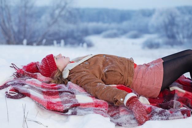 Teen mädchen auf plaid im schnee