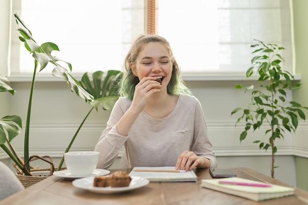 Teen mädchen, das cupcakes isst, tee trinkt, zu hause am tisch sitzt