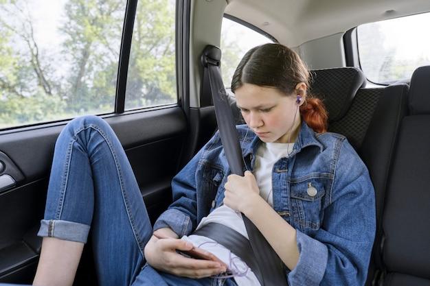 Teen mädchen, das im auto im hinteren beifahrersitz mit smartphone und kopfhörern sitzt