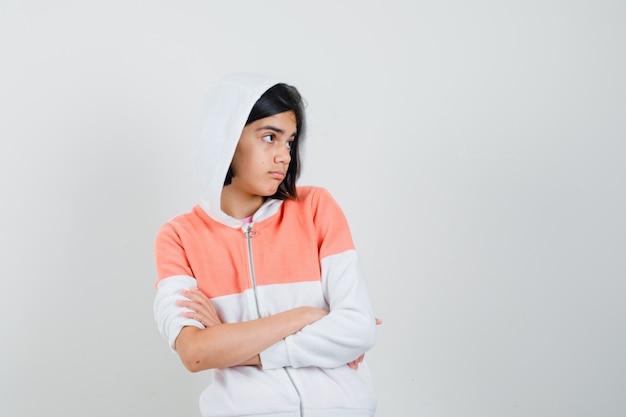 Teen mädchen, das mit verschränkten armen steht, während weg im sweatshirt schaut und zweifelhaft schaut.