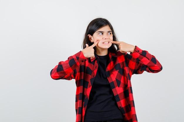 Teen mädchen drückt finger auf wangen in t-shirt, kariertem hemd und schaut fokussiert. vorderansicht.