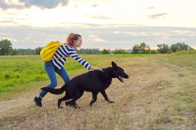 Teen mädchen haustier besitzer spielen und sprechen mit großen schwarzen schäferhund