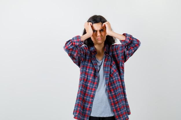 Teen mädchen im karierten hemd händchen haltend in der nähe von gesicht und mürrisch aussehend, vorderansicht.