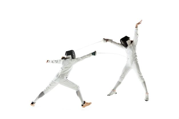 Teen mädchen in fechtkostümen mit schwertern in den händen lokalisiert auf weißem studiohintergrund. junge weibliche models üben und trainieren in bewegung, aktion. copyspace. sport, jugend, gesunder lebensstil.