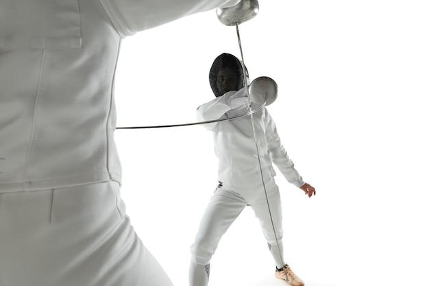Teen mädchen in fechtkostümen mit schwertern in den händen lokalisiert auf weißem studiohintergrund. junge weibliche models üben und trainieren in bewegung, aktion. copyspace.