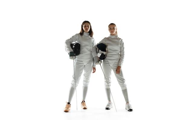 Teen mädchen in fechtkostümen mit schwertern in händen lokalisiert auf weißer studiowand