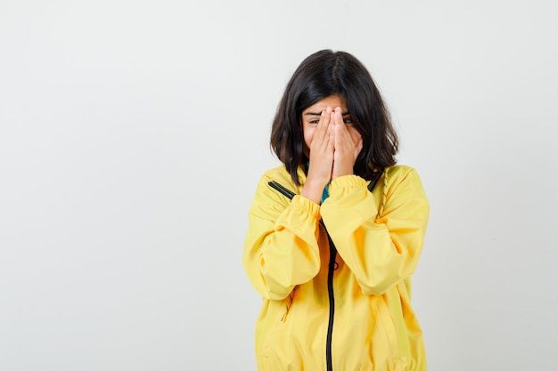 Teen mädchen in gelber jacke händchen haltend im gesicht und ängstlich aussehend, vorderansicht.