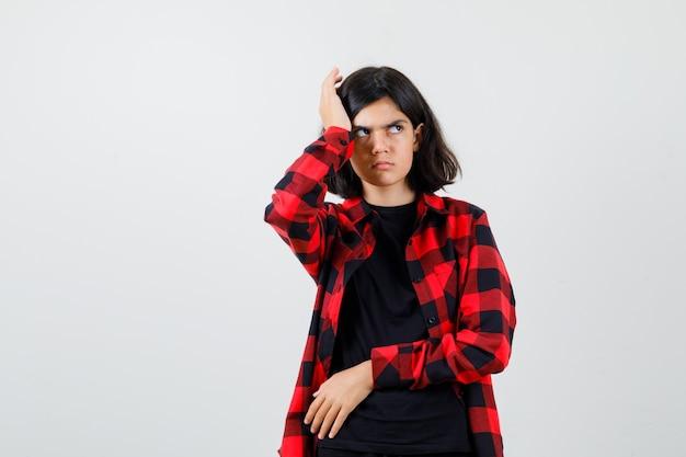 Teen mädchen kratzt sich am kopf, während sie im t-shirt, kariertem hemd beiseite schaut und wütend aussieht, vorderansicht.