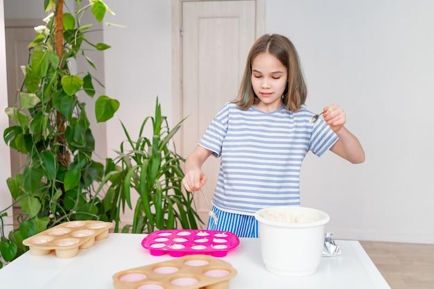 Teen mädchen legt den teig in silikonform für cupcakes. einfache und leckere dessertrezepte. kulinarisches hobby. junger koch.