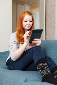 Teen mädchen liest e-book oder tablet-computer