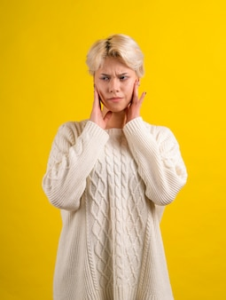 Teen mädchen mit kurzem weißen haarschnitt, der weißen strickpullover trägt, hat zahnschmerzen