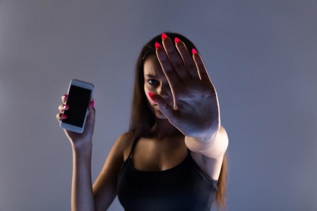 Teen mädchen übermäßig am telefon zu hause sitzen. er ist ein opfer von online-mobbing in sozialen netzwerken von stalker.