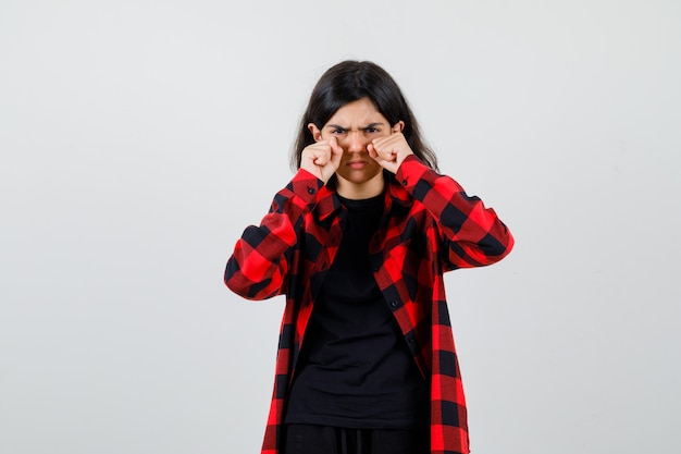 Teen mädchen weint, während sie sich die augen mit fäusten im t-shirt, kariertem hemd reibt und traurig aussieht. vorderansicht.