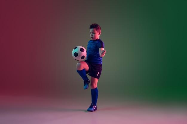 Teen männlicher fußball oder fußballspieler, junge auf gradientenhintergrund im neonlicht - bewegung, aktion, aktivitätskonzept