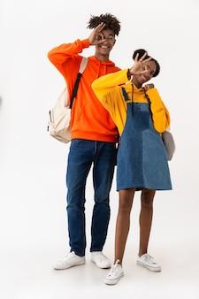 Teen paar in bunten kleidern lächelnd, während ok zeichen angezeigt, lokalisiert über weiße wand