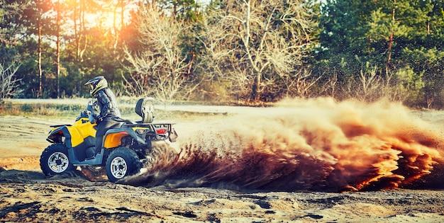Teen reitet atv in sanddünen und macht eine kurve im sand