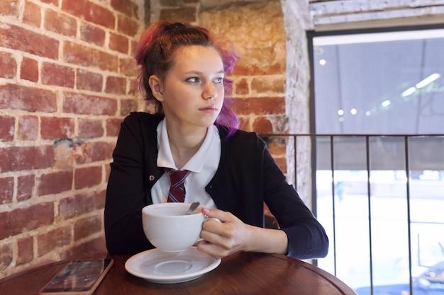 Teen schulmädchen sitzt in einem café mit einer tasse cappuccino