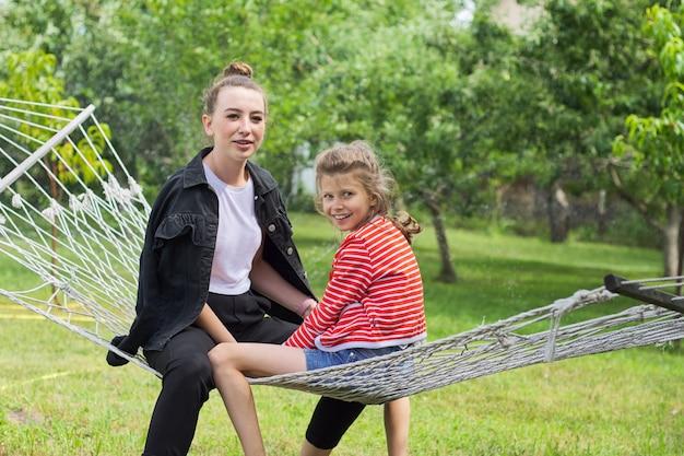 Teen schwester mädchen und kind spaß auf hängematte im hinterhof garten