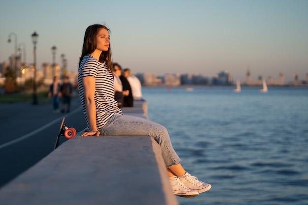 Teen skater mädchen bei sonnenuntergang am meer junge frau genießen sommerabend am fluss oder meer blick auf wasser