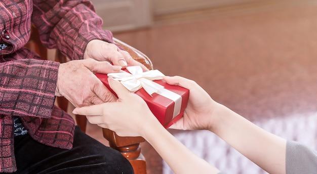 Teenage asia girl gibt oma, die auf stuhl schöne geschenkbox für muttertag geburtstagsfeier idee zu hause mit dunklem hintergrund, nahaufnahme, kopie raum, beschnittene ansicht sitzt