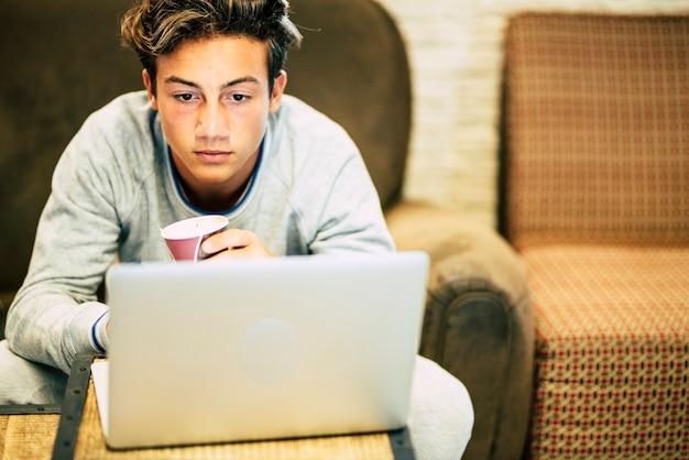 Teenager allein zu hause auf dem sofa mit seinem laptop beim arbeiten oder spielen oder anschauen von videos - nacht mit kaffee und brille auf dem tisch