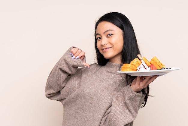 Teenager asiatisches mädchen, das waffeln auf beige wand stolz und selbstzufrieden hält