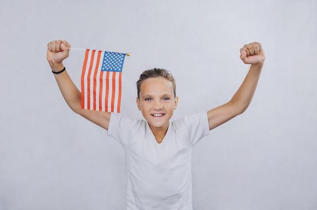 Teenager auf einem hellen hintergrund, der eine amerikanische flagge in seinen händen hält.