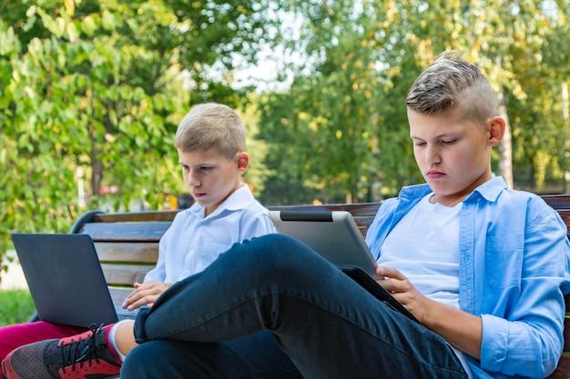 Teenager auf parkbank mit laptop und digitalem tablet