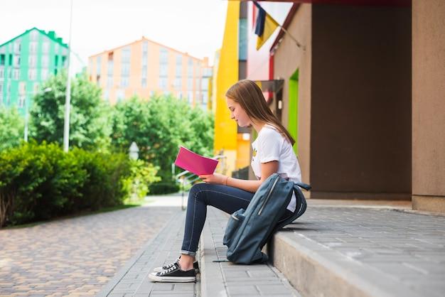 Teenager auf veranda lesen notizblock