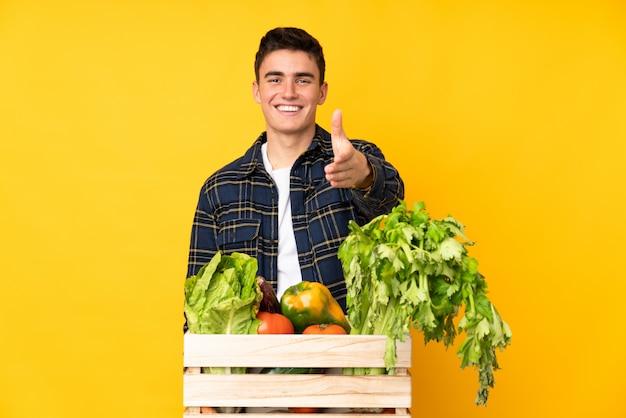 Teenager-bauernmann mit frisch gepflücktem gemüse in einem kastenhandschlag nach vielem