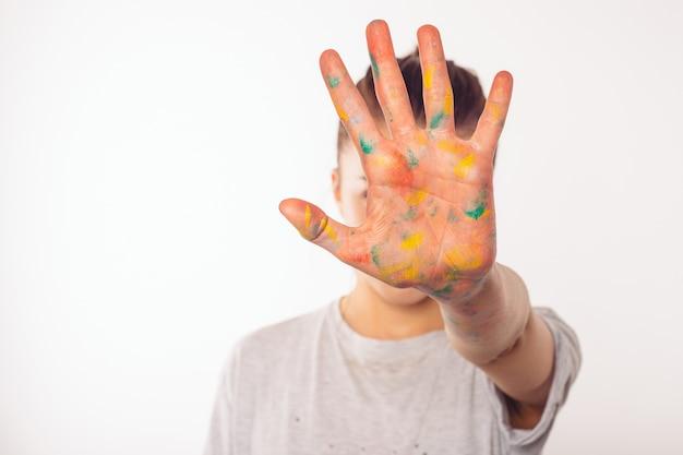 Teenager bedeckt ihr gesicht mit ihrer rechten handfläche in farbe